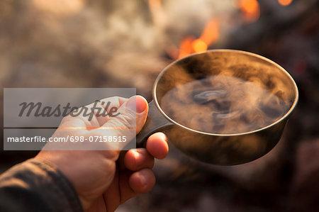 Camper holding mug with bonfire in background