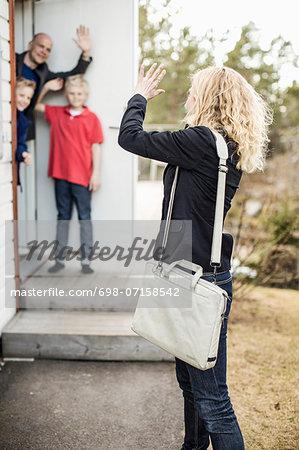 Woman waving goodbye to family