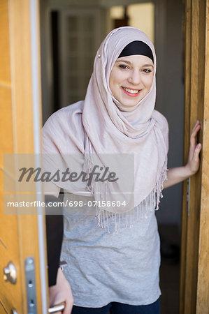 Portrait of smiling young woman standing by open door