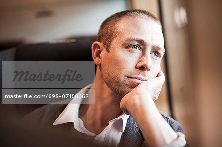Thoughtful mature businessman sitting in train