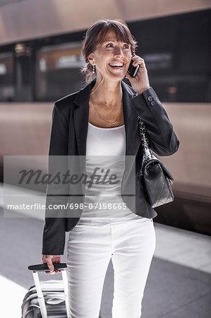 Happy businesswoman using mobile phone on railroad station platform