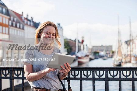 Happy woman using digital tablet against railing at harbor