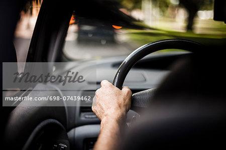 Man's hand driving car