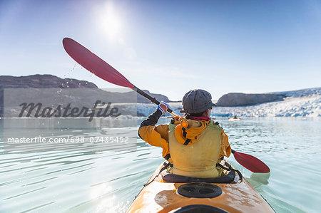 Rear view of mature woman kayaking on sea