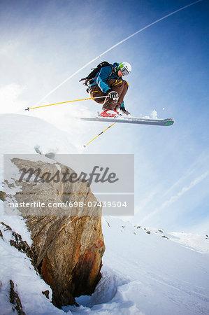 Full length of free ride skier in mid air against sky