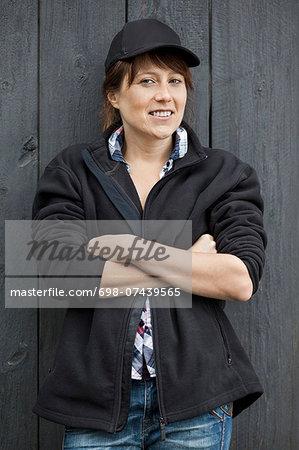 Portrait of confident female farmer standing arms crossed against barn door