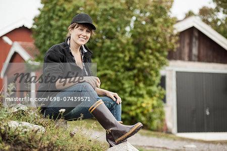 Full length portrait of confident female farmer sitting on rock at farm