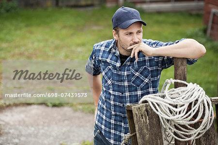 Thoughtful farmer leaning on railing at farm