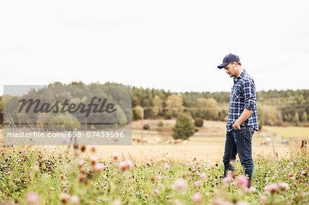 Side view of mid adult farmer walking on field