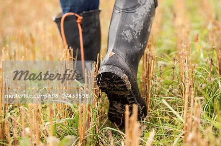 Low section of farmer walking in field