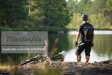 Rear view of mountain biker looking at lake