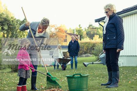 Multi-generation family raking autumn leaves at yard