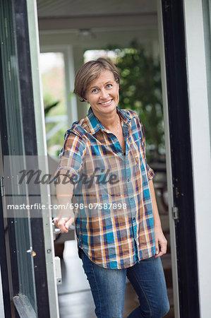 Portrait of mature woman opening door of house