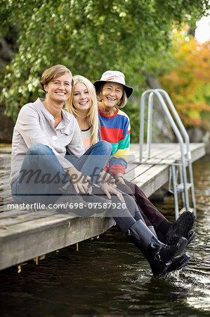 Portrait of three generation females sitting on pier