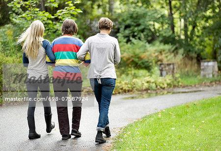 Rear view of three generation females walking on street at park