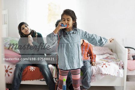 Muslim family listening to girl singing in bedroom