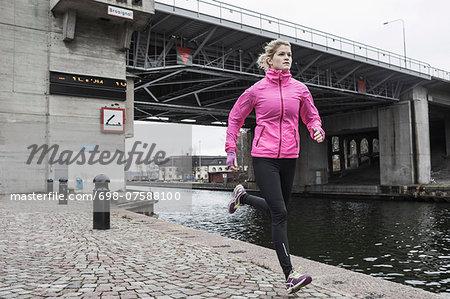 Full length of woman jogging against bridge