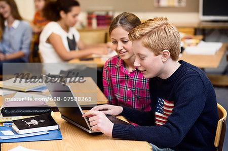School students using laptop in classroom