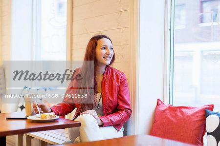 Happy teenage girl looking away at cafe