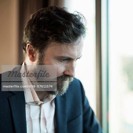 Businessman looking down by window in hotel room