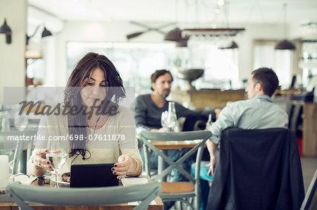 Businesswoman using digital tablet in restaurant
