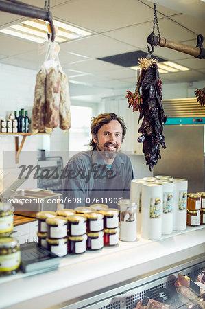Portrait of confident mature salesman at supermarket counter