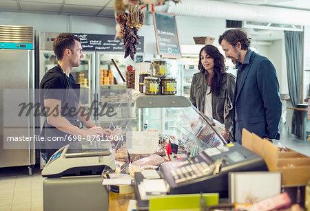 Salesman attending couple in supermarket