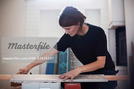 Female carpenter measuring wooden plank