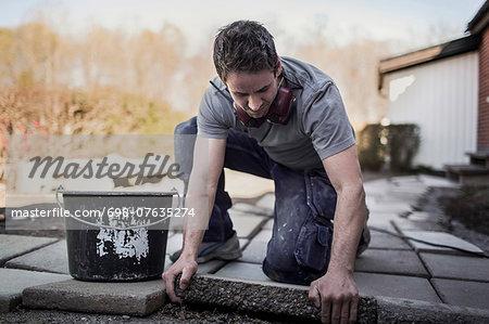 Carpenter positioning stone tile in yard