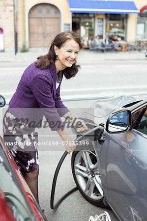 Smiling senior woman refueling car on street