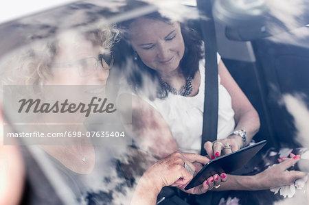 Senior women using digital tablet in car