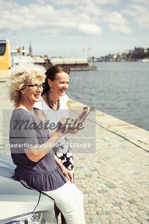 Happy senior women leaning on car at riverbank