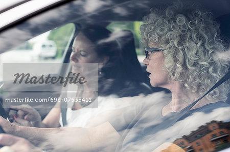Senior women discussing over digital tablet in car