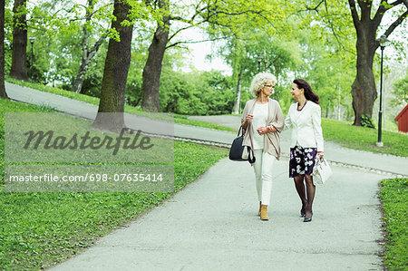 Full length of senior women walking on garden path