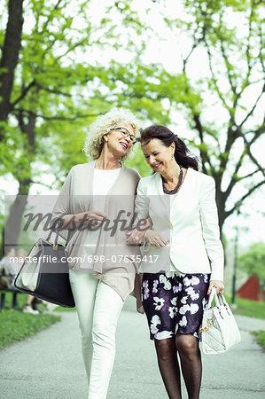 Happy senior female friends walking on garden path