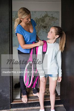 Mother assisting daughter in carrying tennis bag at doorway