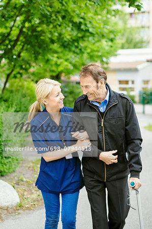 Happy female caretaker walking with disabled senior man on street