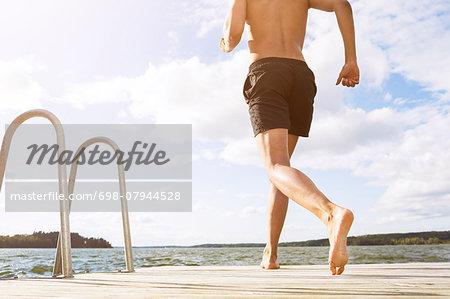 Low section of man running on boardwalk at lake