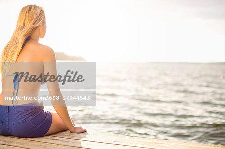 Rear view of woman in bikini top sitting on boardwalk by lake against sky