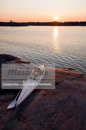 Kayak moored on rocks during sunset