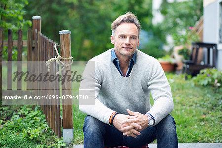 Portrait of smiling mature man sitting in yard