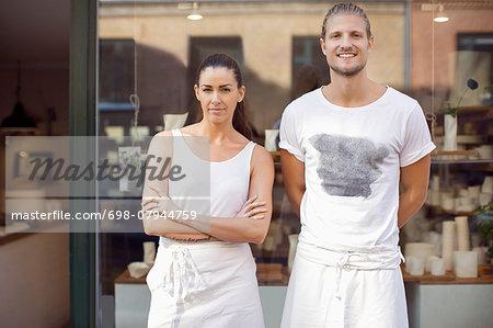 Portrait of smiling workers standing outside crockery workshop