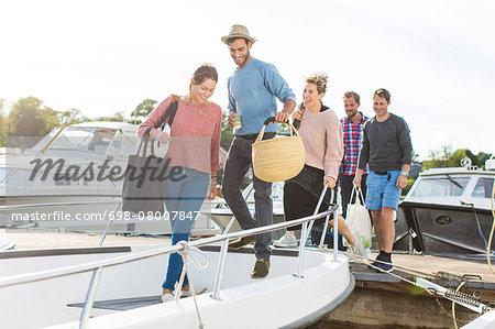 Friends boarding yacht against sky