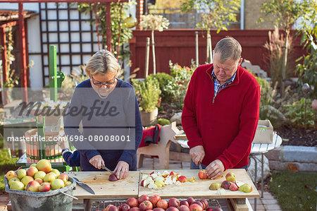 Senior couple cutting fresh apples at yard