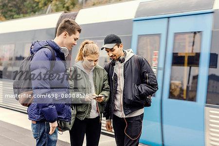 Multi ethnic university students using mobile phone at subway station