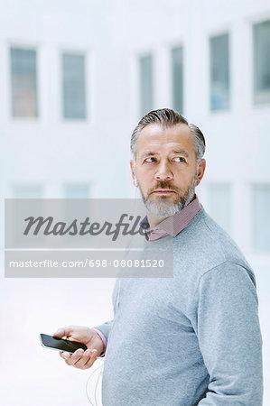 Businessman looking away listening music through smart phone in office