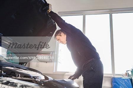 Mechanic opening car's hood in auto repair shop