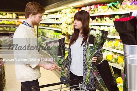 Couple buying flowers at supermarket