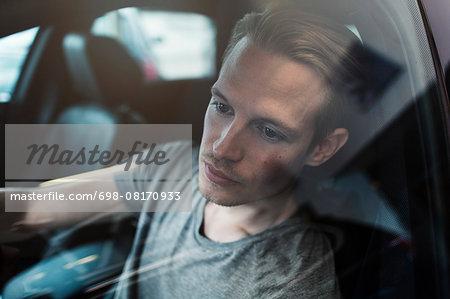 Man sitting in car at dealership shop