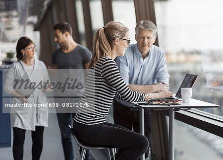 Business people working by window in office